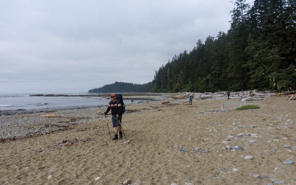 Hikers walking on a sandy beach near Darling River on the West Coast Trail