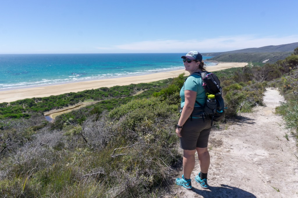 Female hiker wearing a backpack on a trail near the ocean in Narawantapu National Park in Tasmania, Australia