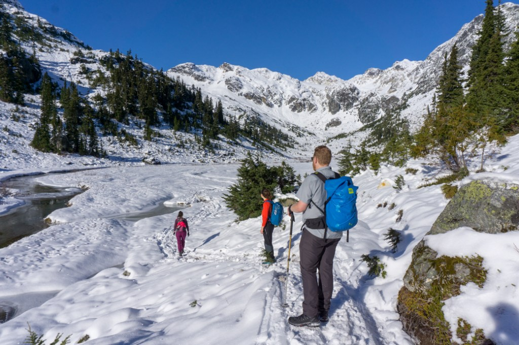 Hikers cross a snowy valley with some open water in a stream