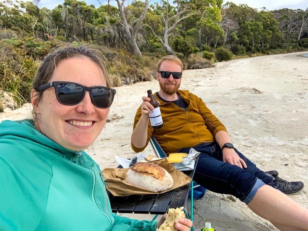 A man and a woman eat bread and cheese on a sandy beach