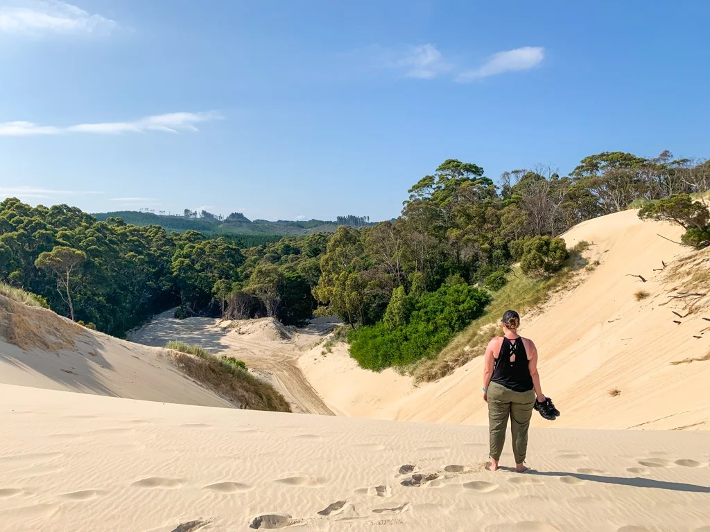 Woman standing on a dune at Henty Dunes in Tasmania