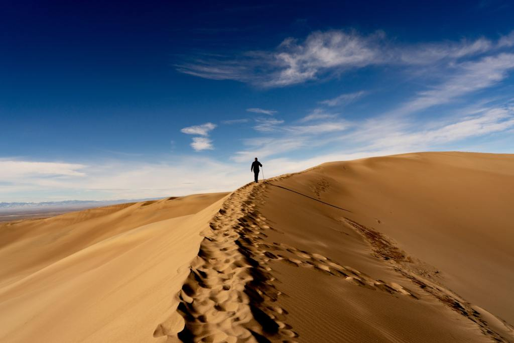 A hiker walks up a sand dune against a blue sky in Great Sand Dunes National Park in Colorado