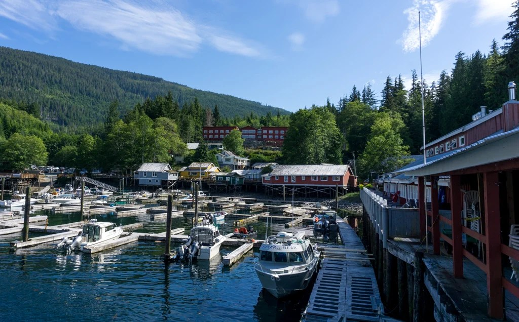 Buildings along the boardwalk and boats in the marina in Telegraph Cove, BC