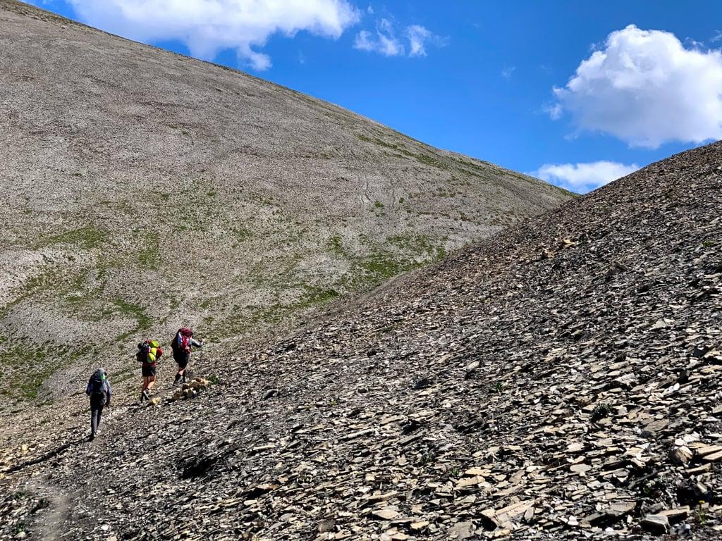 Hikers walking up a scree slope at Numa Pass