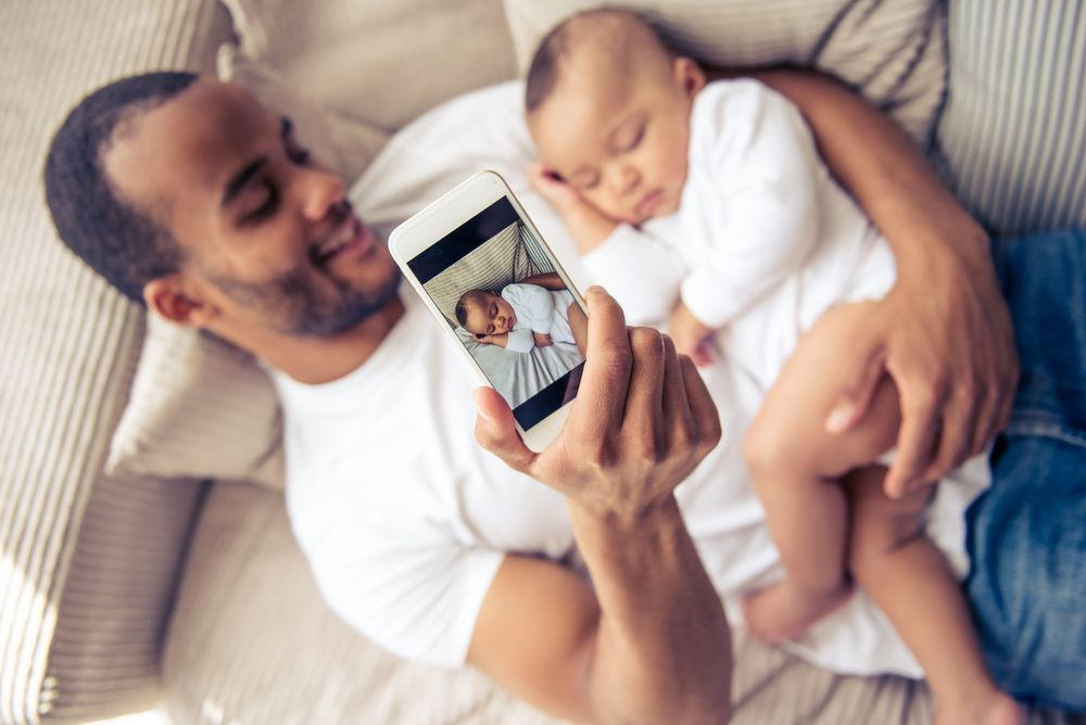 father taking a photo of baby