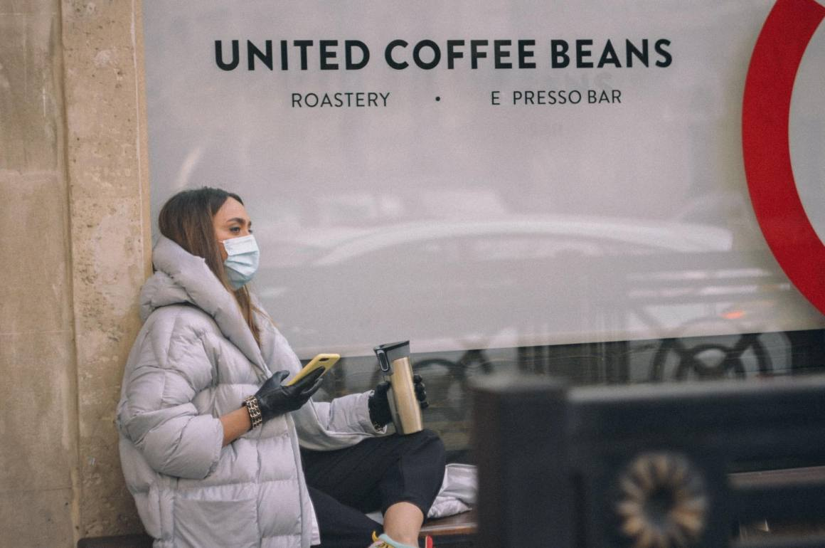 Woman-drinking-coffee-in-a-mask