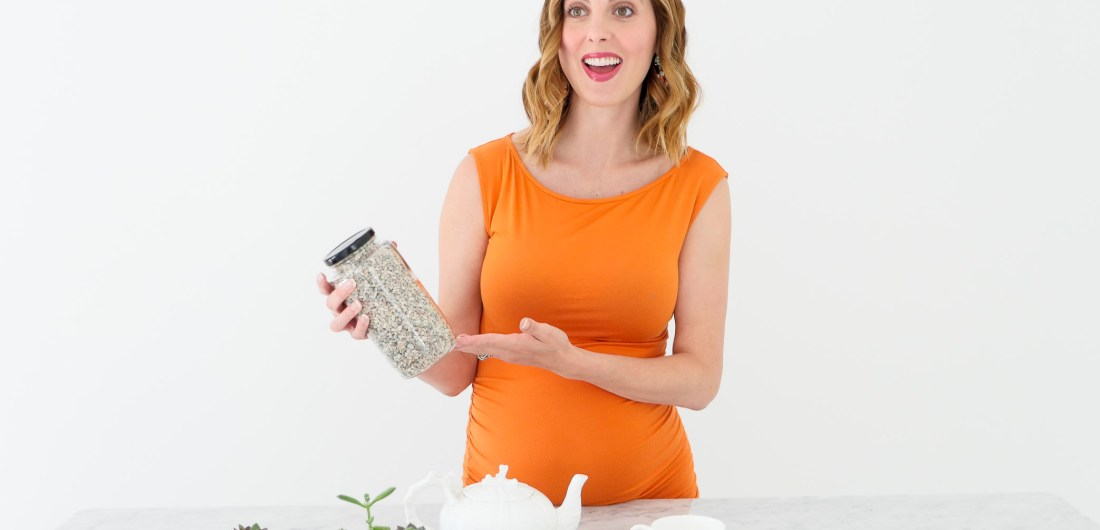 Eva Amurri Martino of lifestyle blog Happily Eva After wearing an orange maternity dress at 34 weeks pregnant shooting a craft segment in her studio in connecticut