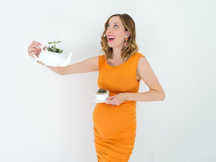 Eva Amurri Martino from the Happily Eva After blog displaying her DIY Teacup Planters with Mini Succulents and small pebbles, wearing a bodycon orange maternity dress, at thirty three weeks pregnant, colorful chandelier earrings, and gold bracelet watch