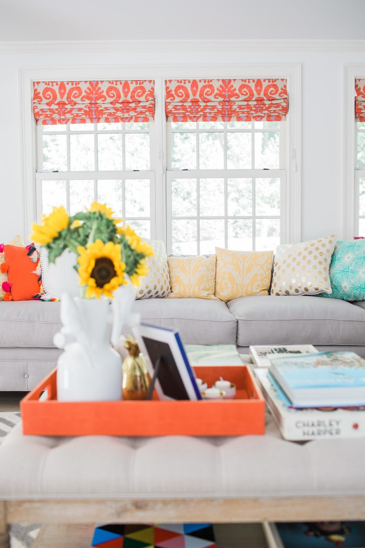 A colorful view of Eva Amurri Martino's Family room couch and coffee table ottoman with custom orange and magenta ikat roman shades