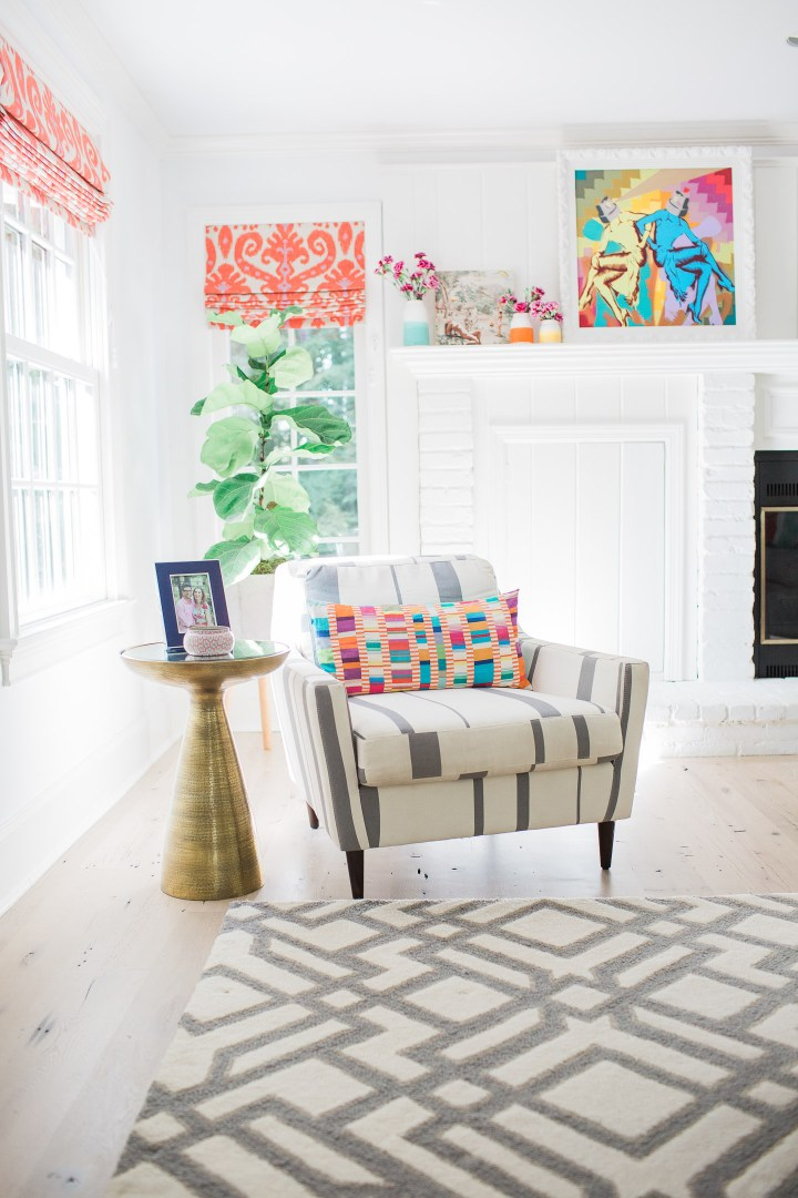 A reading nook in the family room of eva amurri martino's connecticut home, splashes of pattern and orange and magenta custom ikat roman shades