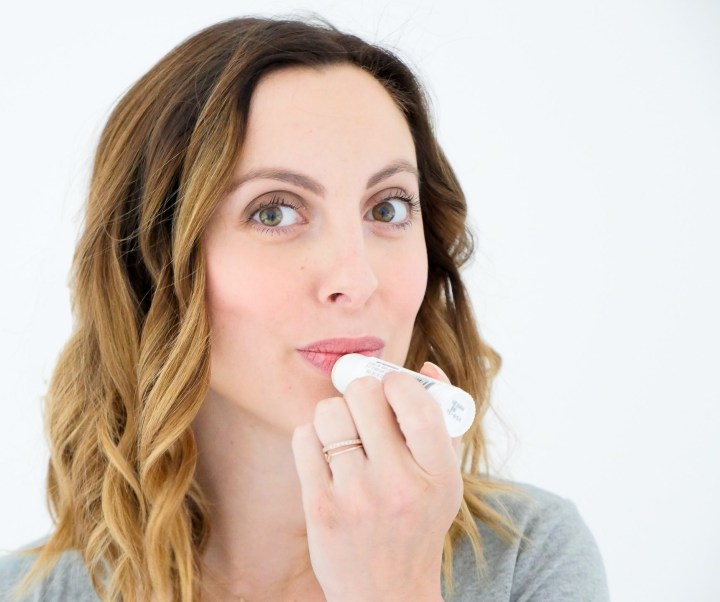 Eva Amurri Martino of lifestyle blog Happily Eva After applying repairing balm to her lips as part of her monthly beauty picks for october