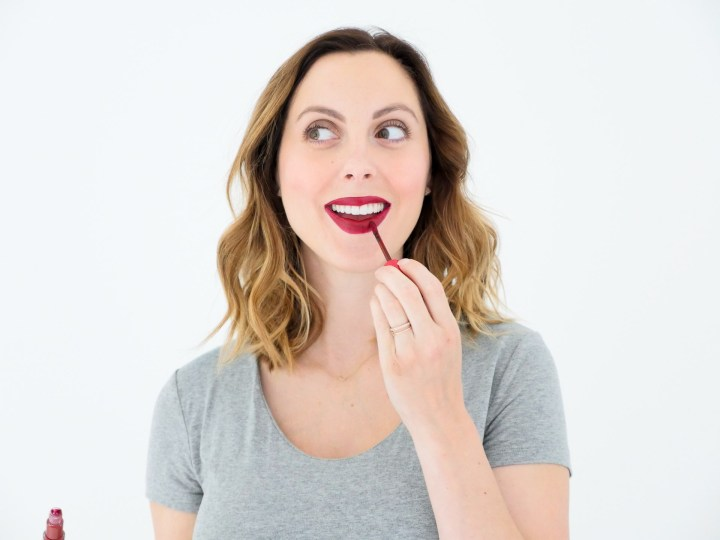 Eva Amurri Martino of lifestyle blog Happily Eva After applying red liquid lipstick as part of her monthly beauty picks for October