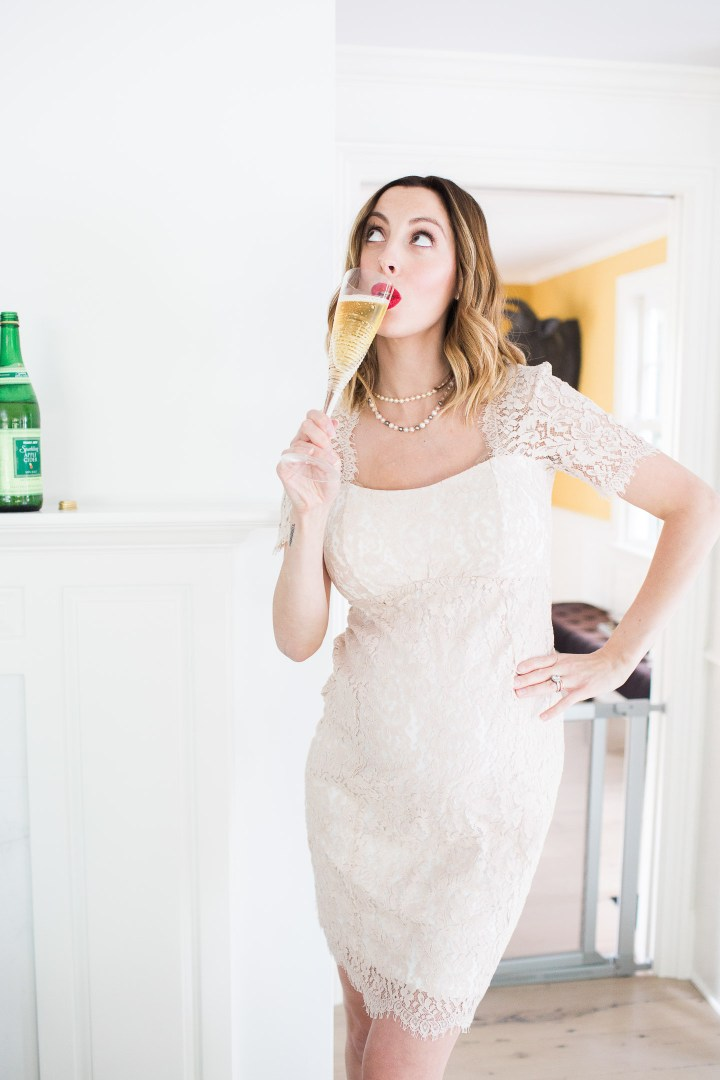 Eva Amurri Martino of lifestyle and motherhood blog Happily Eva After, standing in a champagne colored lace dress and red louboutin platform pumps, holding a glass of sparkling cider in a celebratory toast