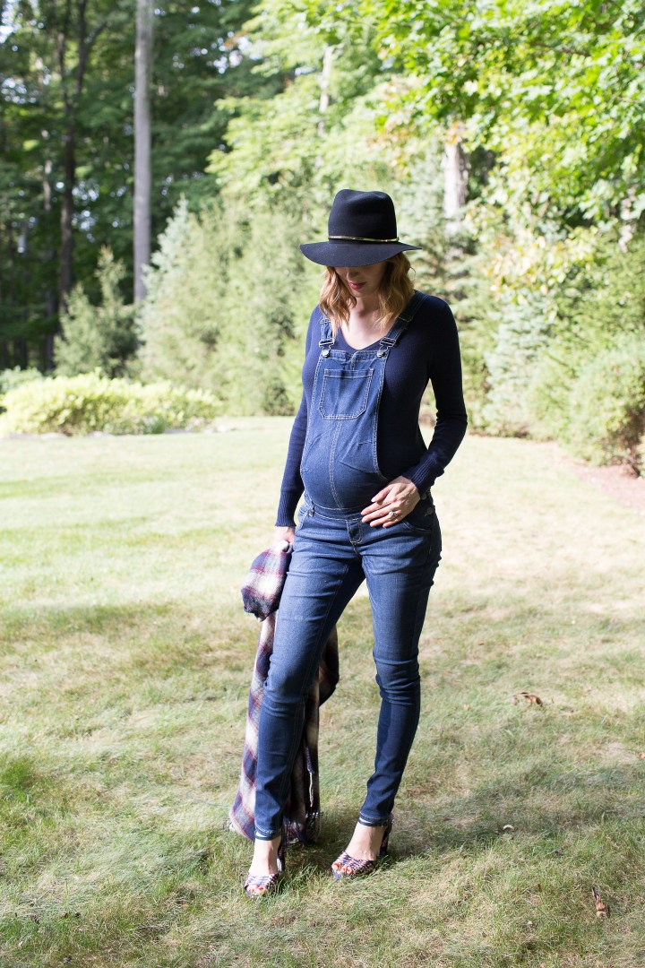 Eva Amurri Martino of lifestyle blog Happily Eva After standing in her yard in maternity overalls, a navy felt hat, and a plaid poncho at her home in connecticut