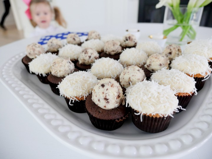 a close up of vanilla and chocolate cupcakes on a white tray