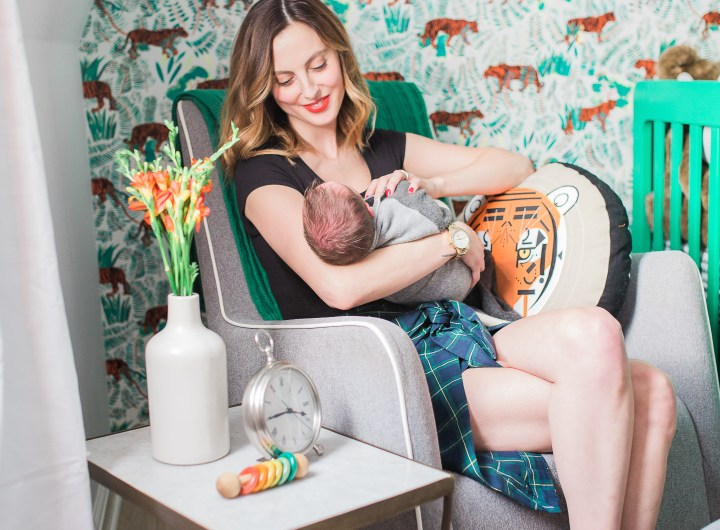 Eva Amurri Martino of lifestyle and motherhood blog Happily Eva After holds her newborn son Major in his newly designed nursery in her connecticut home