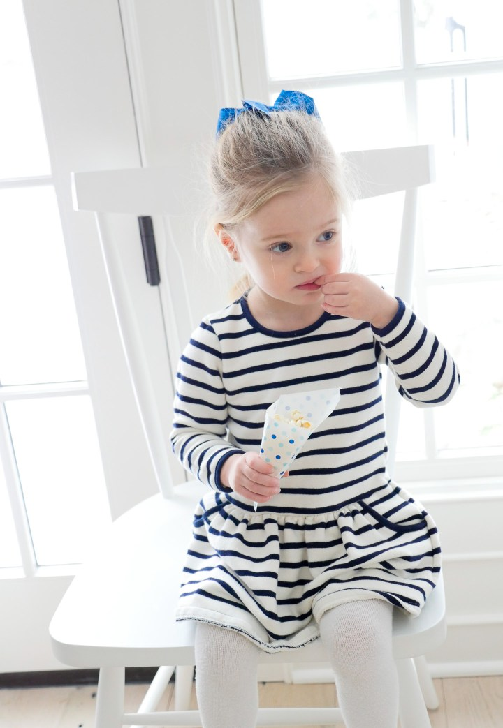 Marlowe Martino wears a striped nautical dress and munches from a cone of popcorn
