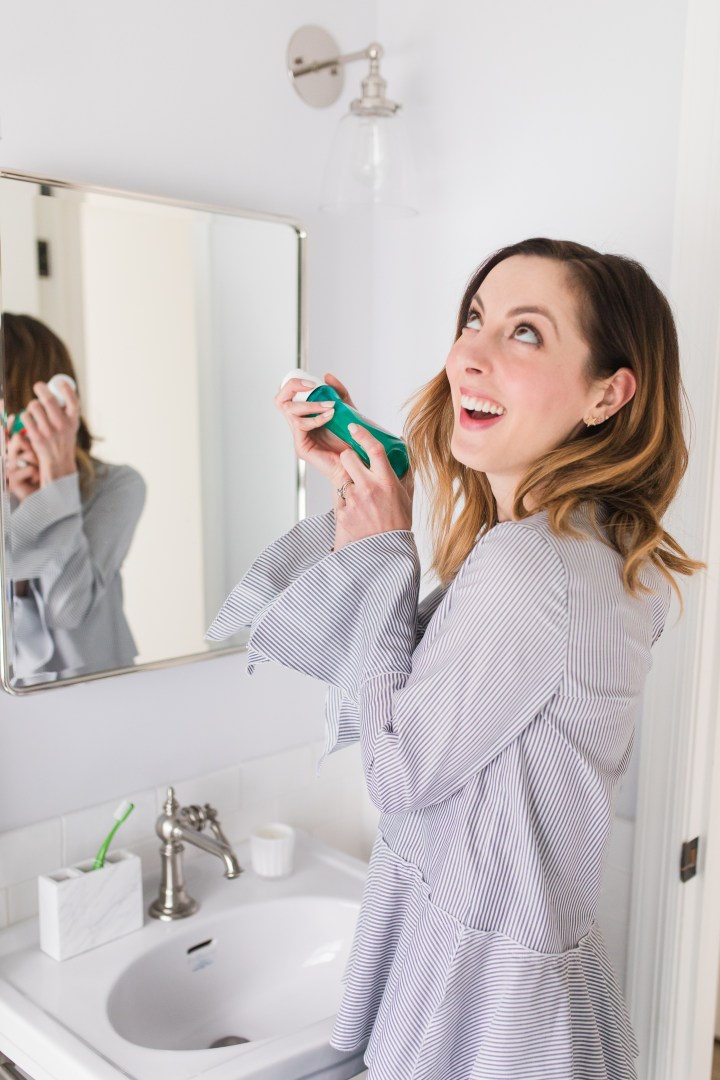 Eva Amurri Martino shakes up a bottle of Colgate Advanced Health mouthwash