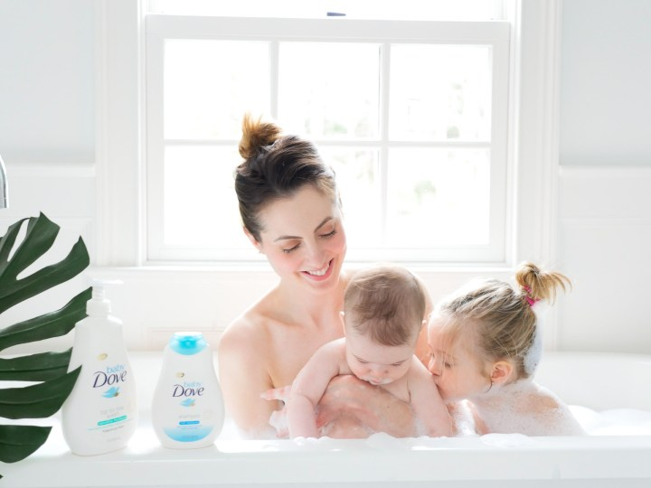 Marlowe Martino gives her baby brother a kiss in the tub