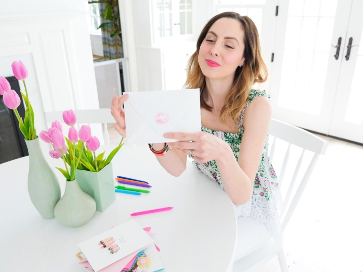 Eva seals her Mother's Day card for her Mom with a pink kiss