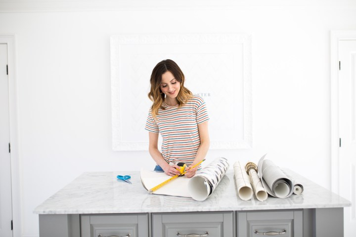 Eva Amurri Martino measures and cuts leftover wallpaper to use in other projects