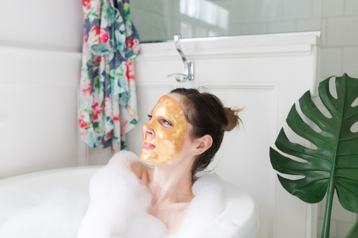 Eva Amurri Martino relaxes in the bath with a gold sheet mask on her face