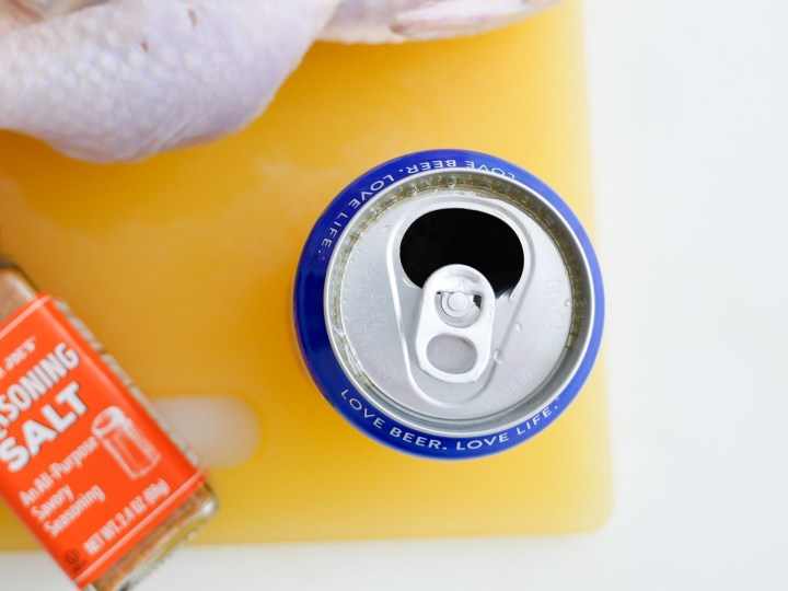 An opened can of beer sits out on a yellow cutting board ready to be made in to beer can chicken