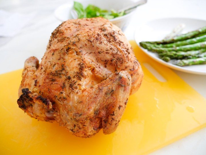 A browned and delicious Beer Can Chicken sits on a yellow cutting board ready to be carved
