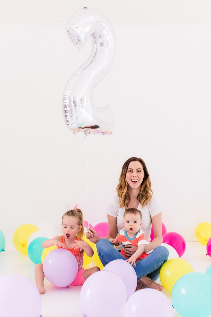 Eva Amurri Martino sits with children Marlowe and Major among tons of multicolored balloons to celebrate the Happily Eva After two year anniversary
