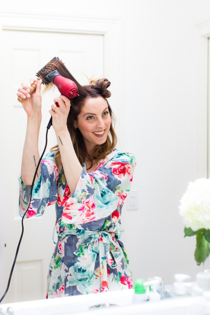 Eva Amurri Martino wears a floral silk robe and gives herself a bouncy blowout in the bathroom of her connecticut home
