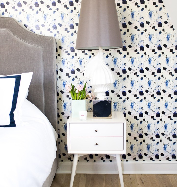 Eva Amurri Martino shows off her guest room revamp, featuring crisp navy and white sheets, midcentury modern bedside tables, a jonathan adler lamp, and kerri rosenthal wallpaper.