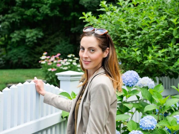 Eva Amurri Martino wears dark denim, brown fringe booties, an olive green sweater and blazer in the garden of her Connecticut home