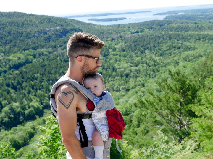 Kyle Martino holds Major Martino in a baby carrier on a hike in Maine