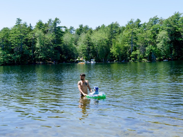 Kyle Martino stands in the lake surrounded by trees