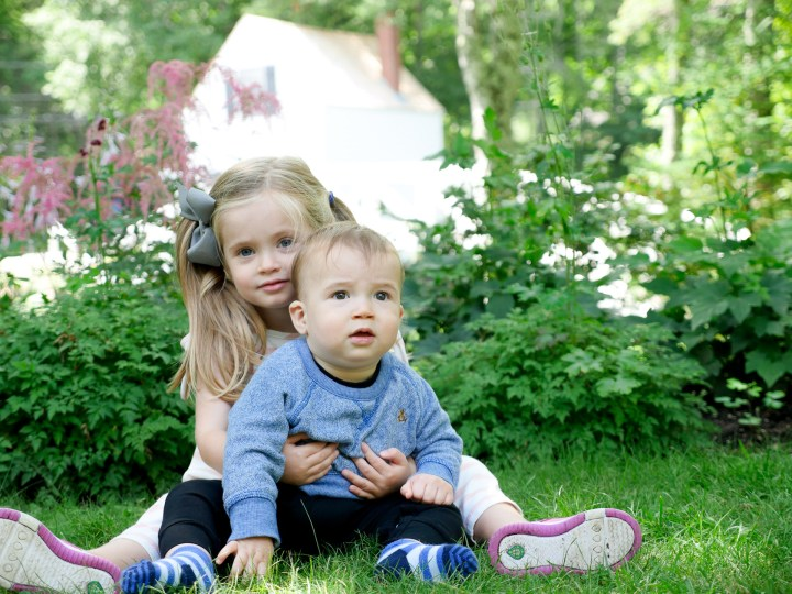 Two year old Marlowe Martino embraces 9 month old brother Major on the grass in Bar Harbor, Maine