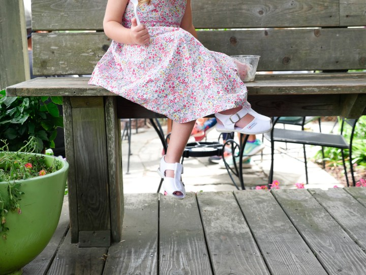Marlowe Martino eats a cup of fresh strawberry ice cream, wearing a flowered summer dress