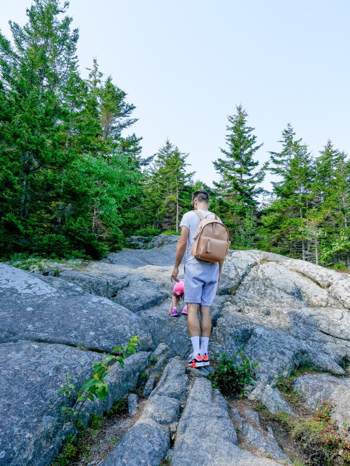 Kyle Martino hikes with two year old daughter Marlowe on a trail in Acadia National Park