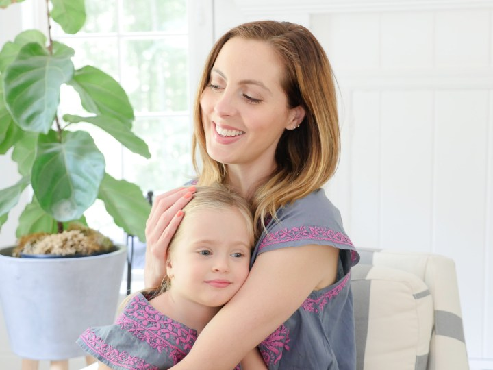 Eva Amurri Martino and Marlowe Martino wear matching embroidered dresses and sit together in a striped armchair in the family room of their Connecticut home