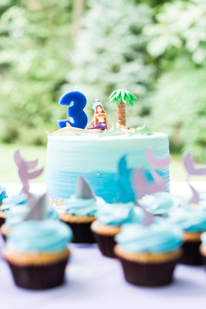 Marlowe Martino's Mermaid and Shark themed birthday cake sits on a table surrounded by cupcakes