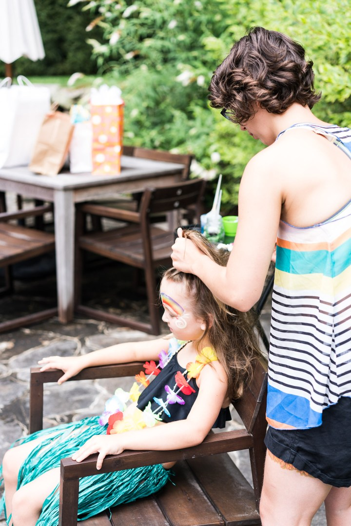 A party guest gets her hair braided at Marlowe Martino's third birthday party