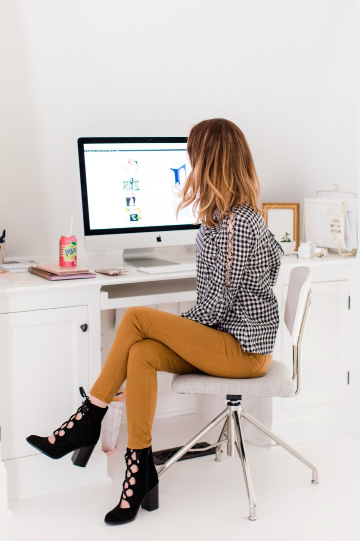 Eva Amurri Martino wears tan jeans and a black and white checked top, and sits at her computer in the Happily Eva After studio