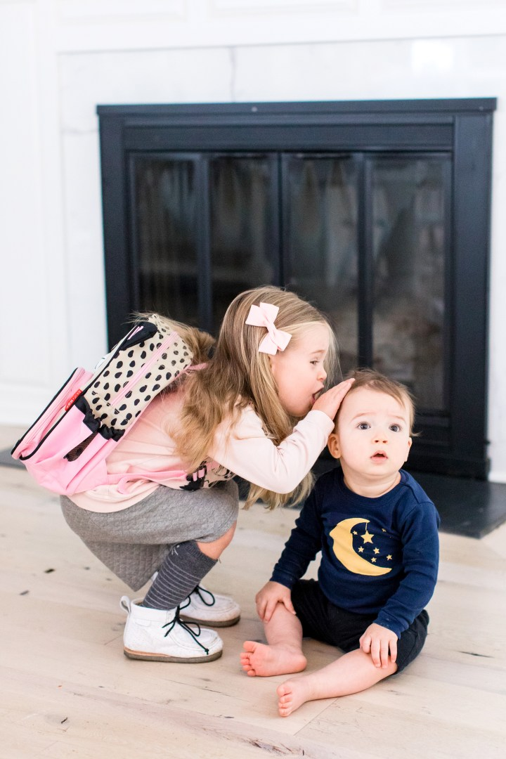 Marlowe Martino wears a pink sweatshirt, grey skirt, and kitty cat backpack as she leans down to pat little brother Major on the head before she heads off to school