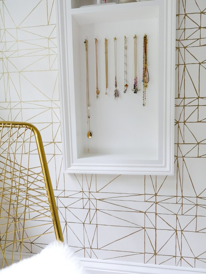 Delicate necklaces hang on gold nails in Eva Amurri Martino's glam room in her Connecticut home
