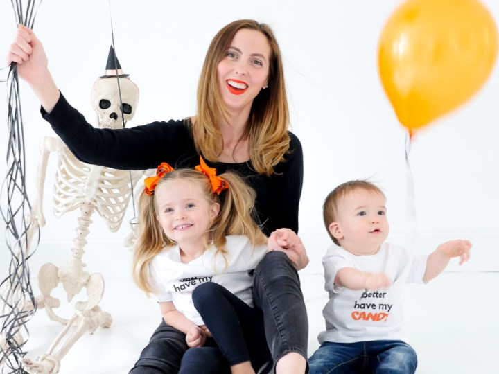 Eva Amurri Martino sits with children Marlowe and Major wearing custom Halloween themed tee shirts designed using The Happily App