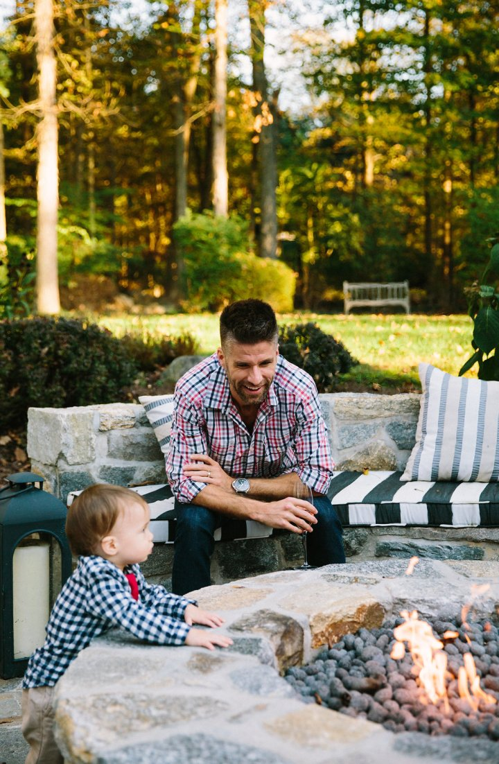 Kyle and Major Martino sit out by the fire pit at their connecticut home for Major's first birthday party