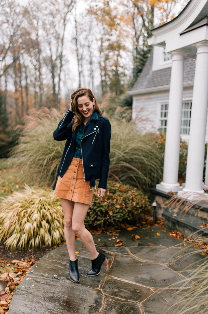 Eva Amurri Martino wears a plaid top, navy blue jacket, corduroy skirt, and black booties and walks down the pathway to her Connecticut home
