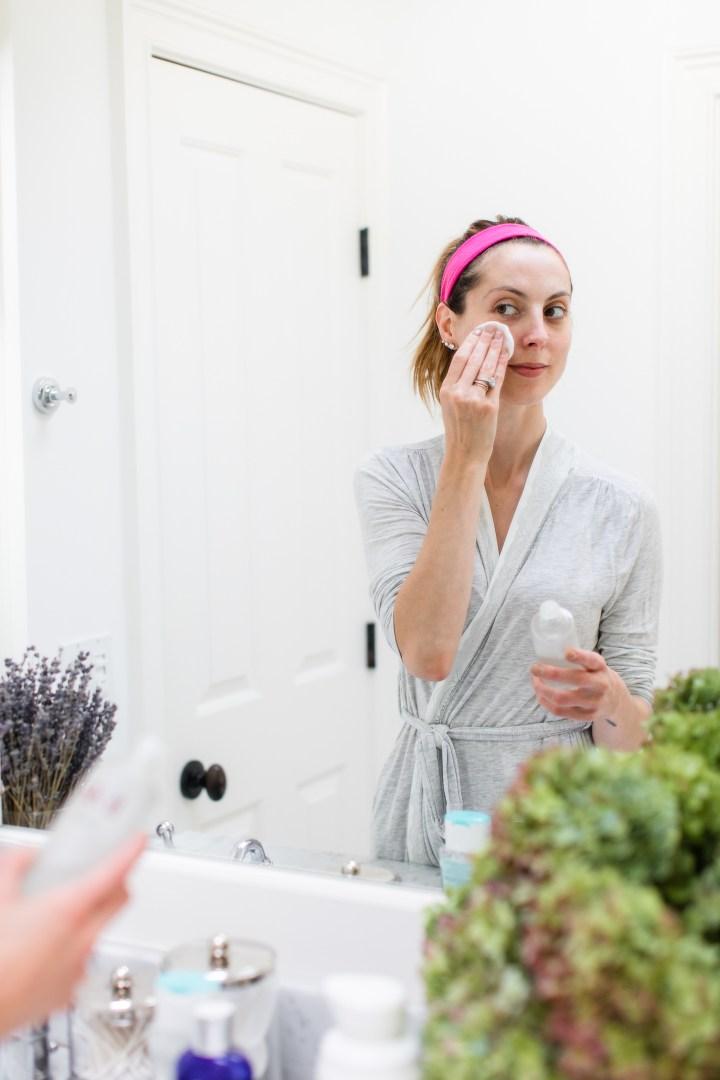 Eva Amurri Martino presses SKII facial treatment essence gently in to her skin using a cotton pad