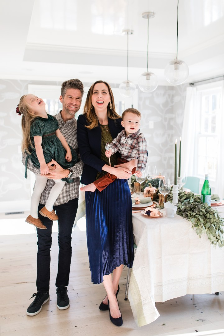 Eva Amurri martino standing with her family, Kyle Martino, Marlowe Martino, and Major Martino, in their dining room set up for Thanksgiving