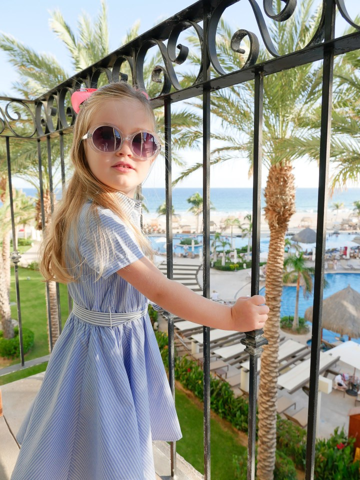 Marlowe Martino stands on the balcony wearing a blue and white dress and sunglasses at the Hyatt Ziva resort in Los Cabos Mexico