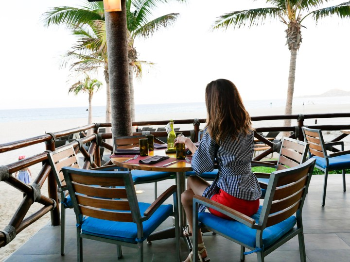 Eva Amurri martino sits outside at a restaurant overlooking the beach in Los Cabos, Mexico